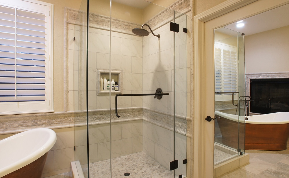 Elegant tile shower with frameless door.