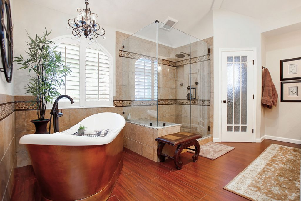 Hammered copper soaking tub and spacious walk-in shower with decorative tile detail.