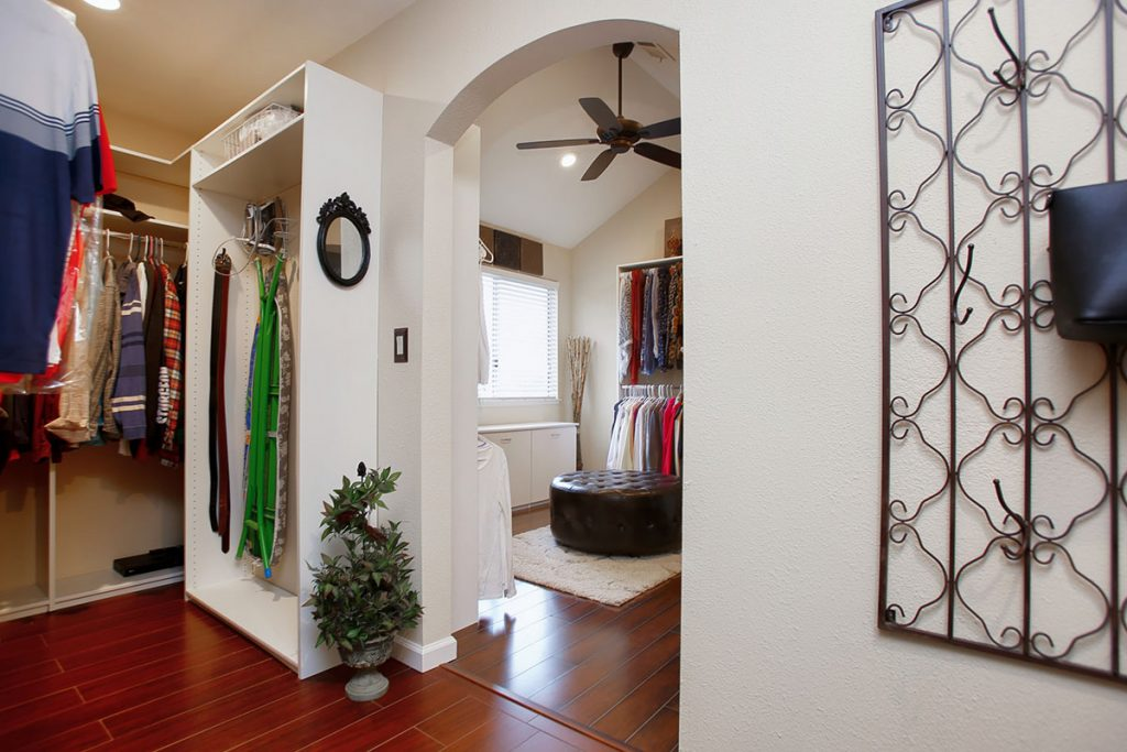 A walk-in closet with storage and space to iron.