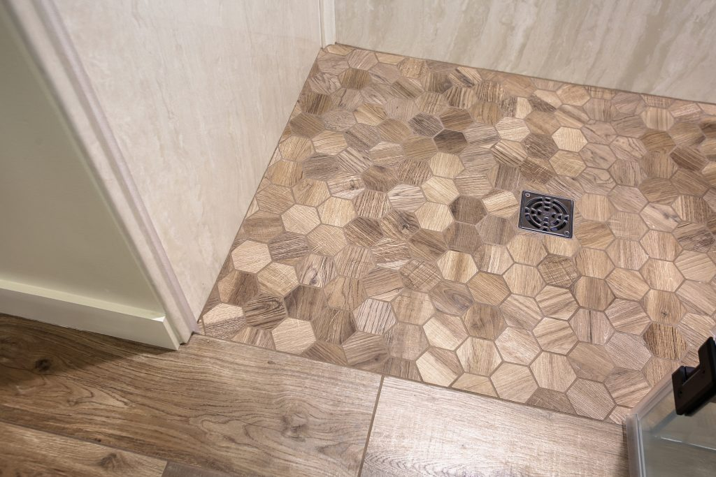 Fashion-forward wood finish tile shower flooring.