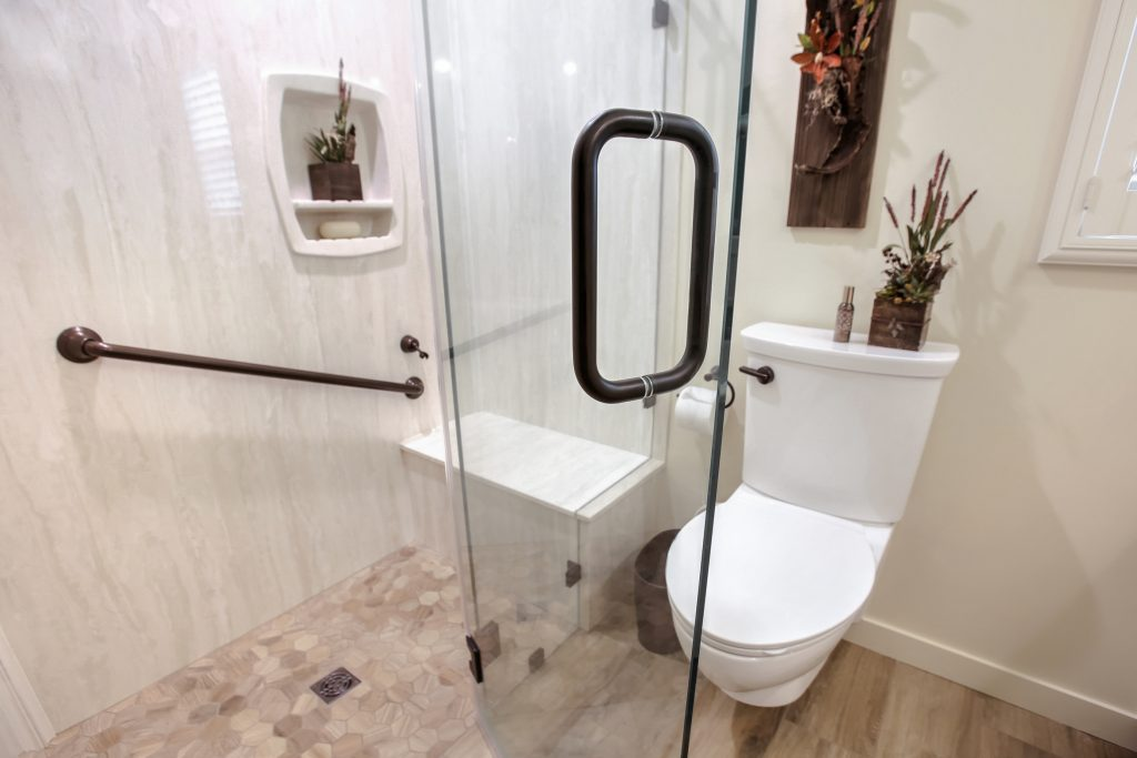 Clear glass shower door with oil rubbed bronze handle.