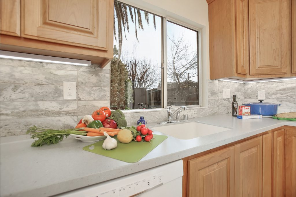 An integral stainless steel sink with a single lever faucet and separate vegetable sprayer.