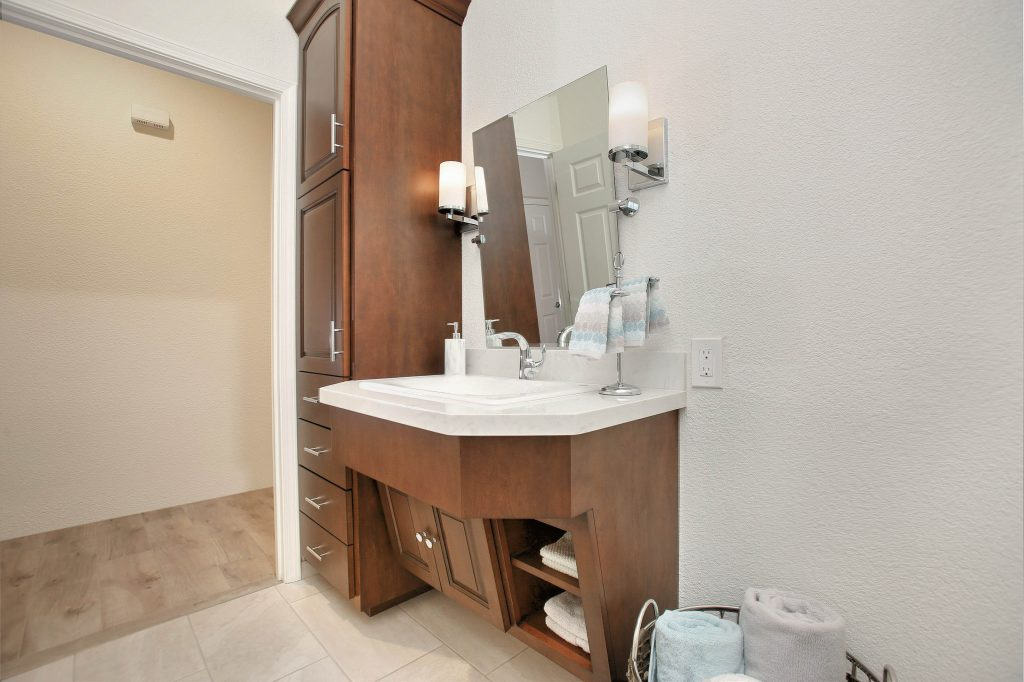 Wider for wheelchair access, custom vanity for wheelchair, pivoting mirror and decorative wall sconces.