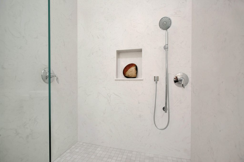 Cultured stone shower walls, decorative tile shower floor, and clear glass shower screen.