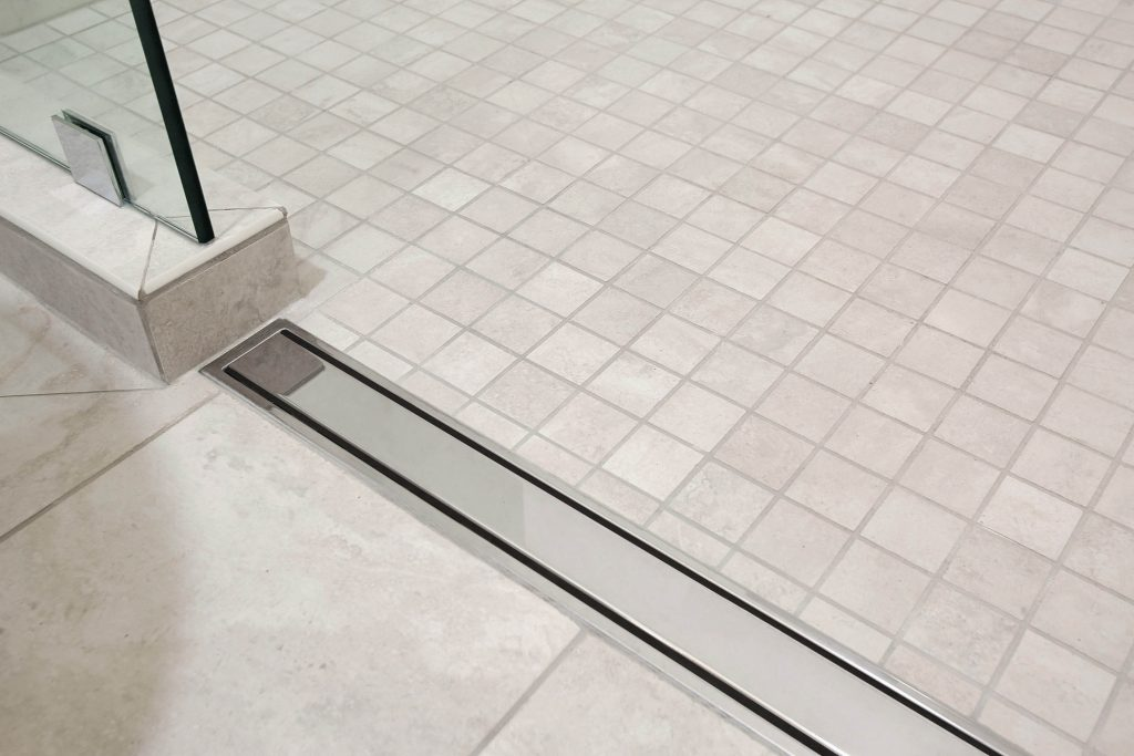 Access friendly walk-in or wheelchair accessible shower with linear drain.