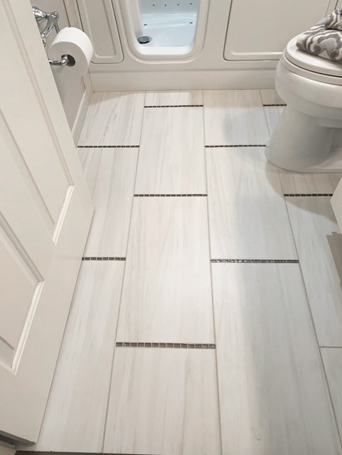 Porcelain tile floor with mosaic glass tile accents make this accessible bathroom as attractive as it is functional.